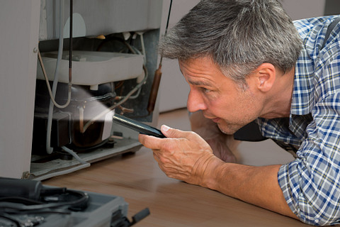 a man checking a machine engine with the Energizer Performance Metal Inspection Pen Light