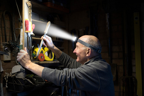 a man wearing an Energizer Vision HD+ Focus Industrial Headlamp organizing his tools