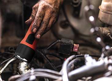 a mechanic checking the car engine with the Energizer Intrinsically Safe Flashlight