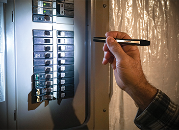a man checking the breaker panel with the Energizer pen flashlight
