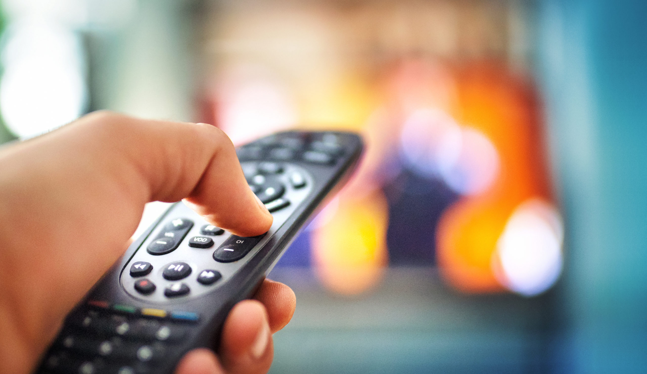 a hand using a tv remote control