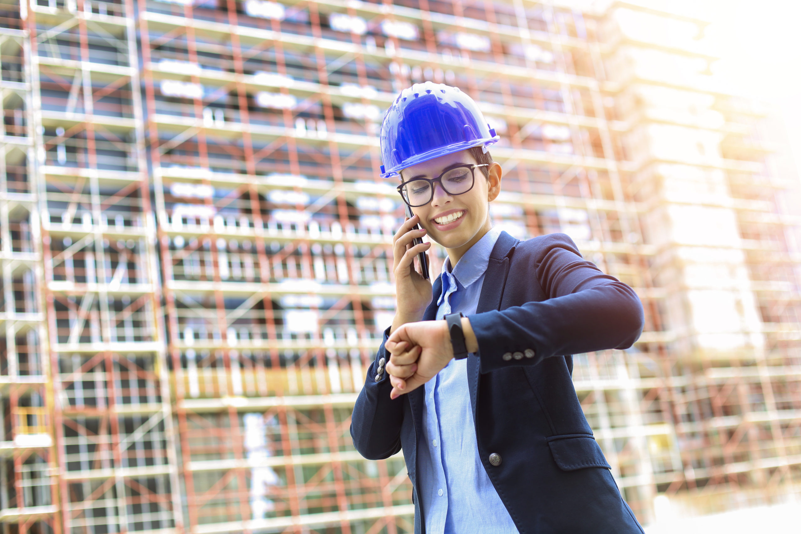a woman with a construction hat talking on the phone and checking the time on her watch