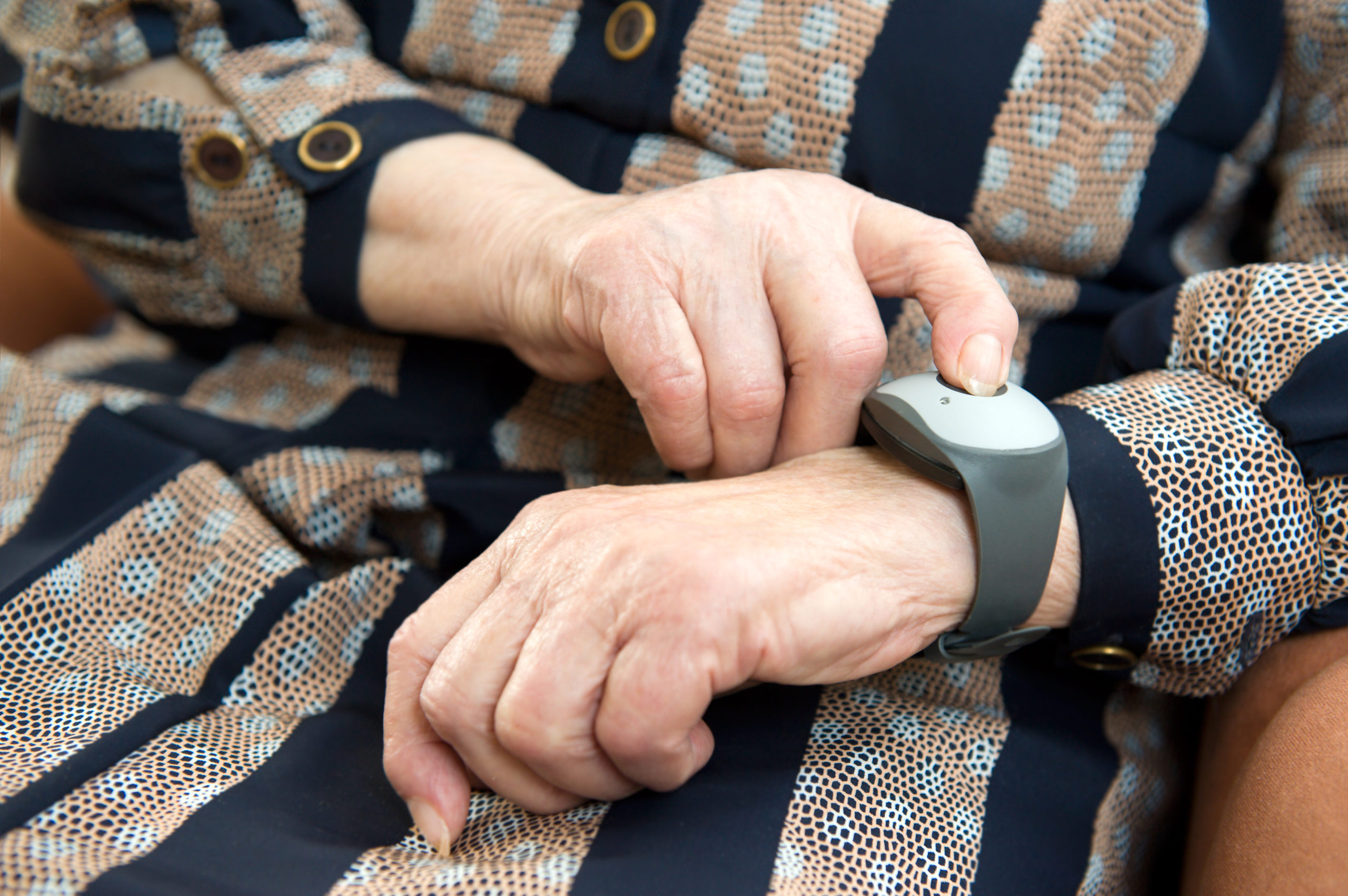 a senior woman pushing the emergency button of the device for professional help