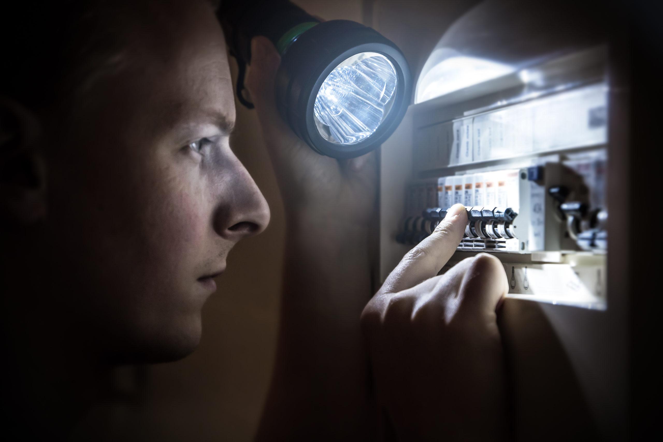 a man holding the Energizer flashlight restoring power on circuit breaker