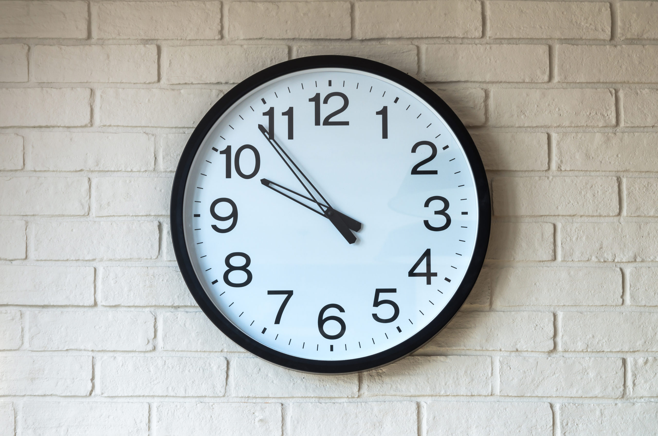 a clock on brick wall displaying the time 9:53