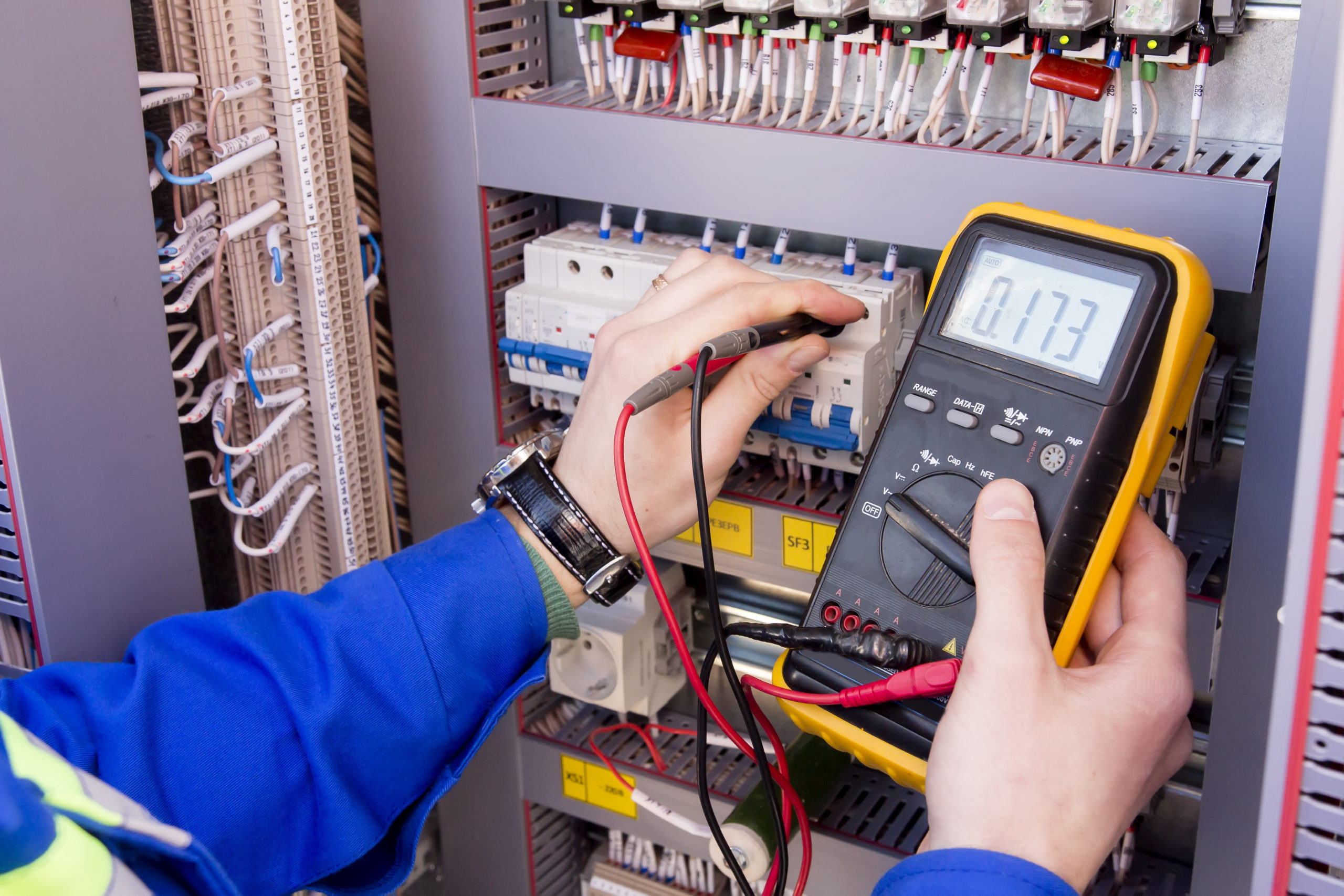 an electrician measuring voltage with a multimeter